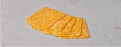 Five slices of monterey colby jack fanned out on white surface