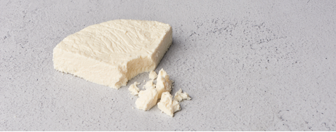 A wedge of queso fresco with the tip crumbled in front of it on a white surface