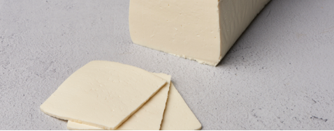 Block of queso blanco with three slices in front on white surface