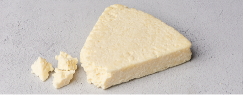 A wedge of Cotija cheese with the tip of the wedge off and crumbled to the left of the wedge